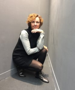woman crouching against the wall