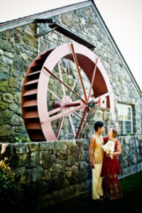 A couple stands in front of the Griffin Museum's water wheel for a wedding