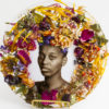 African American woman surrounded by wreath of flowers