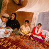 5 young Afghanistan children sit on a floor.
