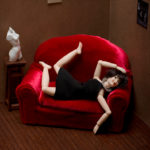 Woman on red couch with limbs akimbo