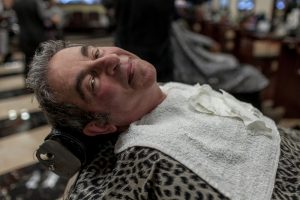 A man leans back on a chair at a salon. He is wearing a cheetah print cover and a hand towel on his chest.