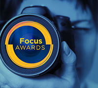 A woman looking through a lens. It is the Focus Logo