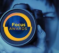 Focus Logo of a woman looking through a camera lens
