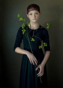 Girl holding green flowers