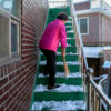 A woman sweeps snow off stairs.