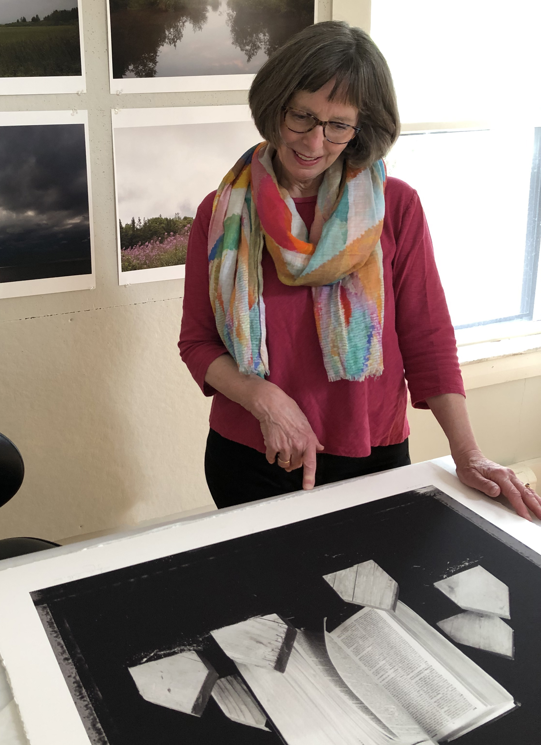 A woman with short hair wearing a scarf points at a photograph laying on a table. There is a grid of landscape photographs pinned to the back wall.