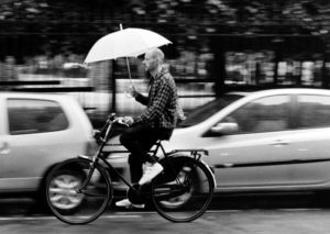 It is raining and a man on bicycle rides in the street with a white umbrella. He passes parked cars. As he is moving he is slightly blurred.