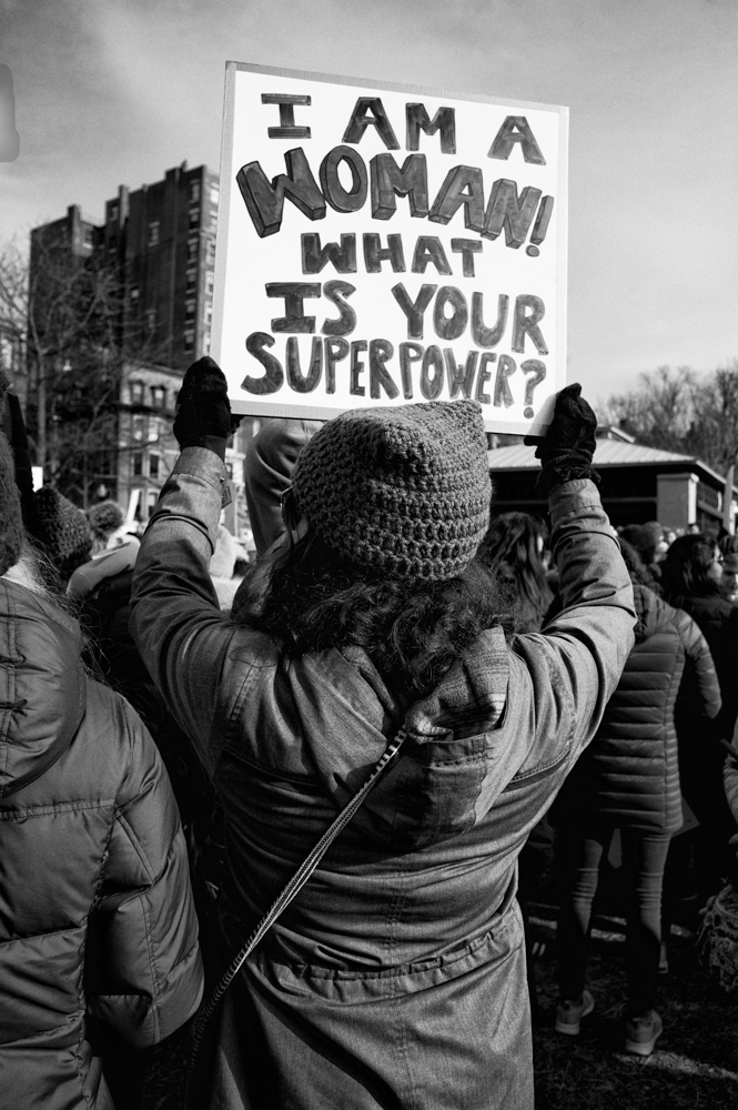 """A woman demonstrator faces away from the viewer holds up a sign that says , """"I am a woman, what is your superpower?"""""""