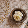 Bowl with flower on a lacy table cloth
