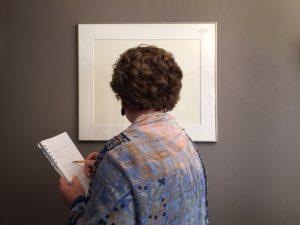 Woman looking at photograph and writing