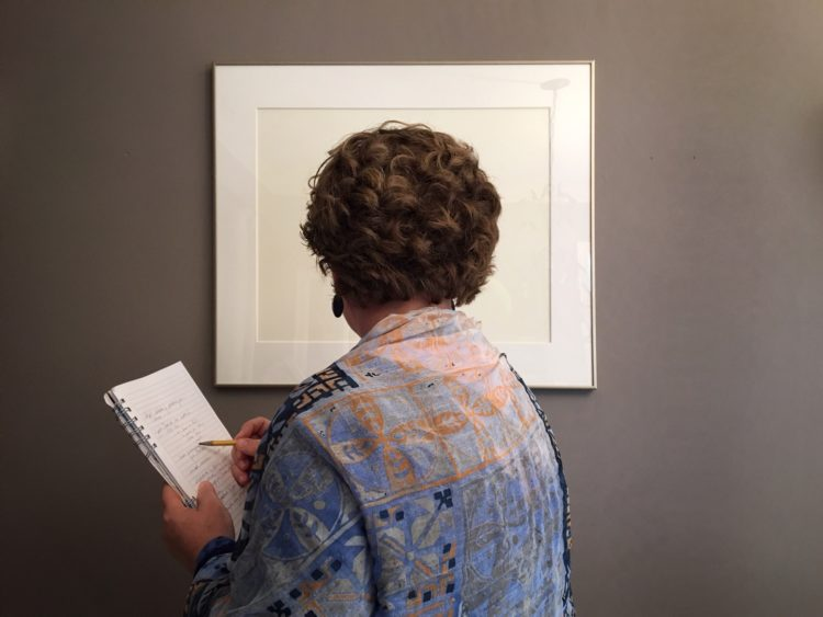 Woman looking at photograph and writing