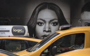 A cab driver passes a large wall mural of a women