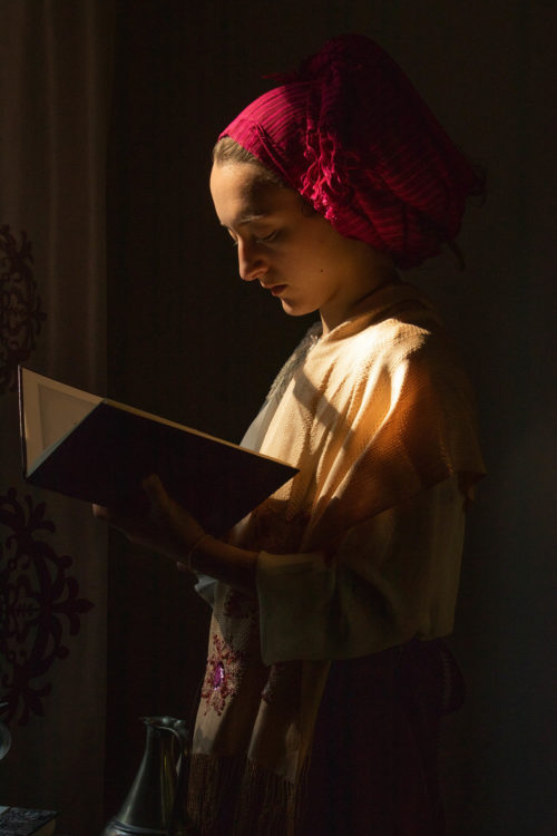 Portrait of young woman reading a book in window light, wearing a headpiece.