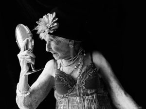 An older woman dressed in lingerie, head dress and jewels looks into a mirror .