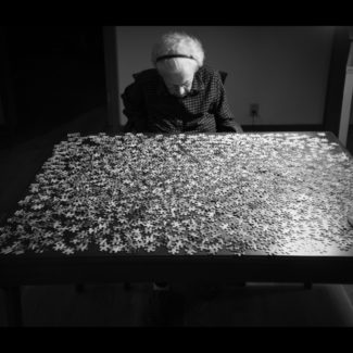 "An older woman sits in front of a jigsaw puzzle unassembled on a table with her head down. © Virgil DiBiase, ""1000 Pieces"""