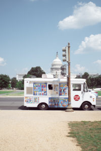 An ice-cream truck in front of the capitol building.