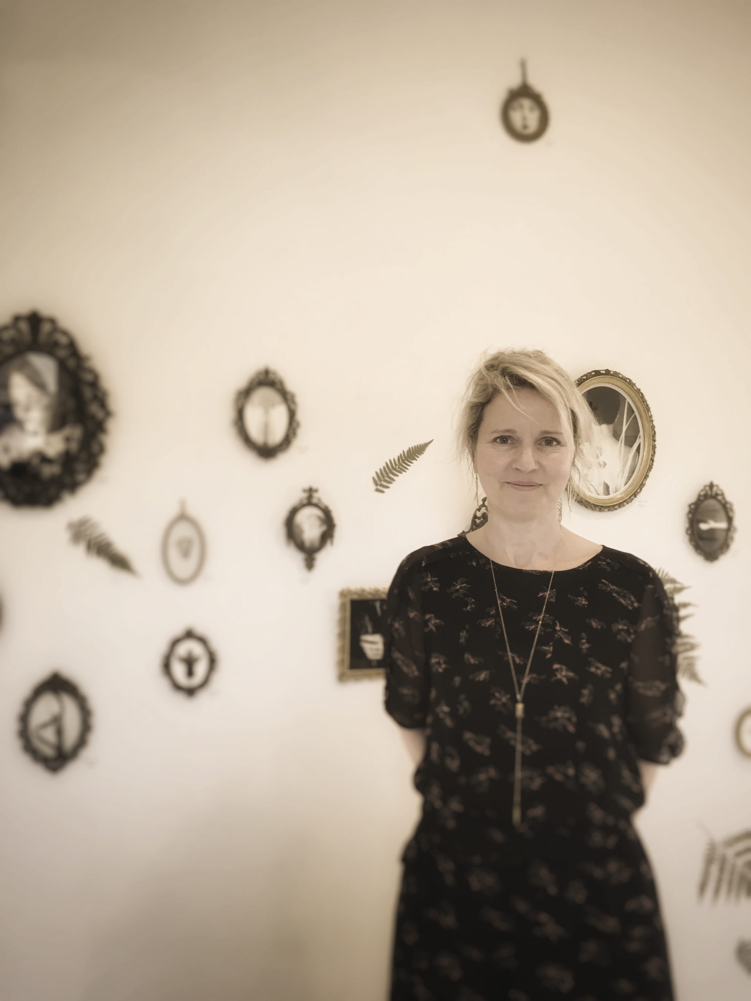 A woman stands in front of a wall full of small frames. She smiles graciously and has her arms around her back.