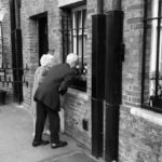 An elderly couple peers into a window and sniffs flowers.
