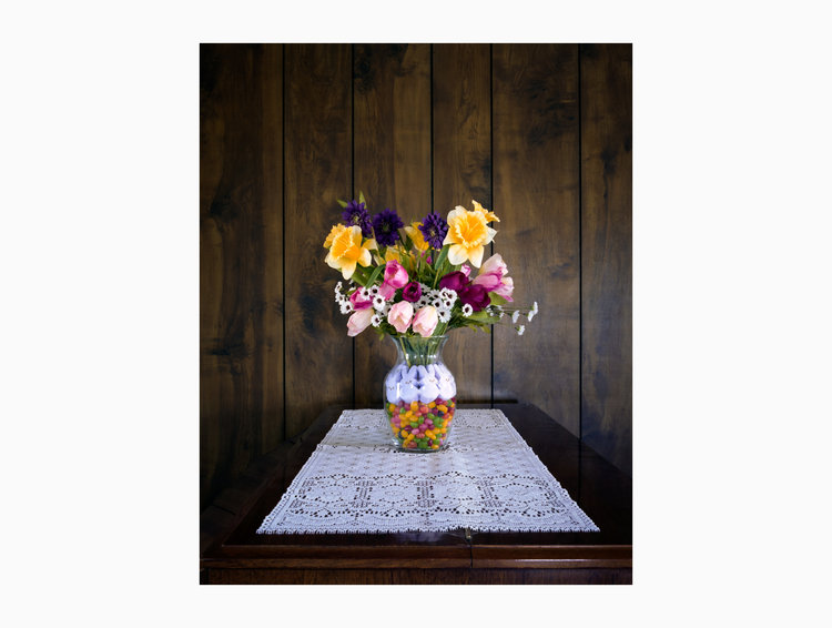 Flowers in a vase on a linen topped table.