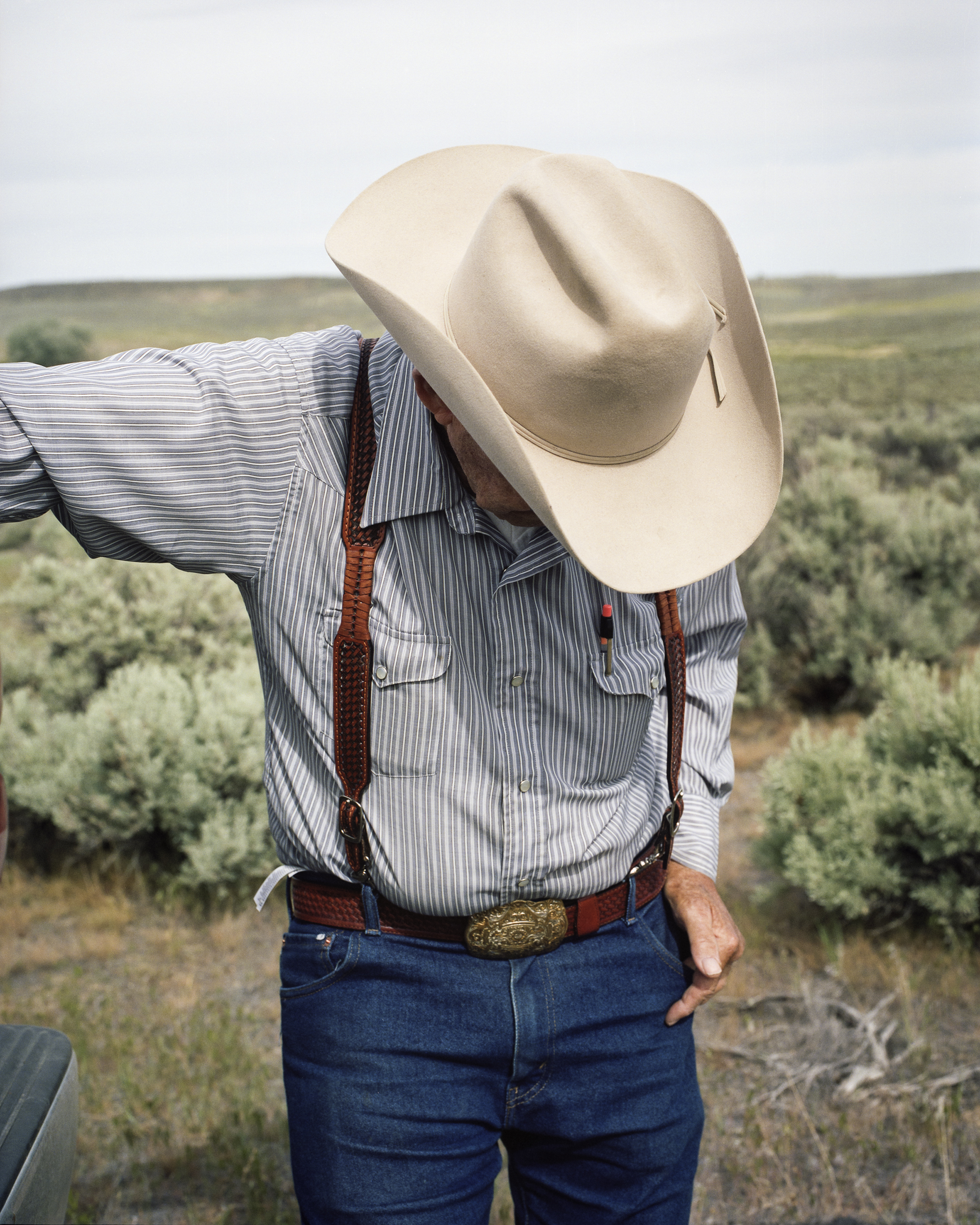 A man in a cowboy hat looking downwards.