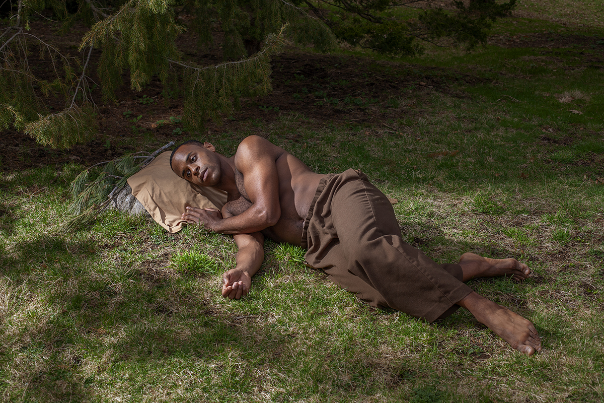 Man lays on the grass and rests his head on a boulder