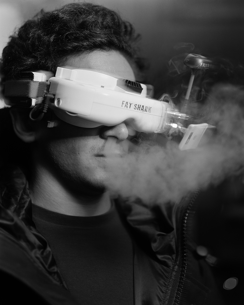 A man blowing out smoke from his nose while wearing a robotic head ware