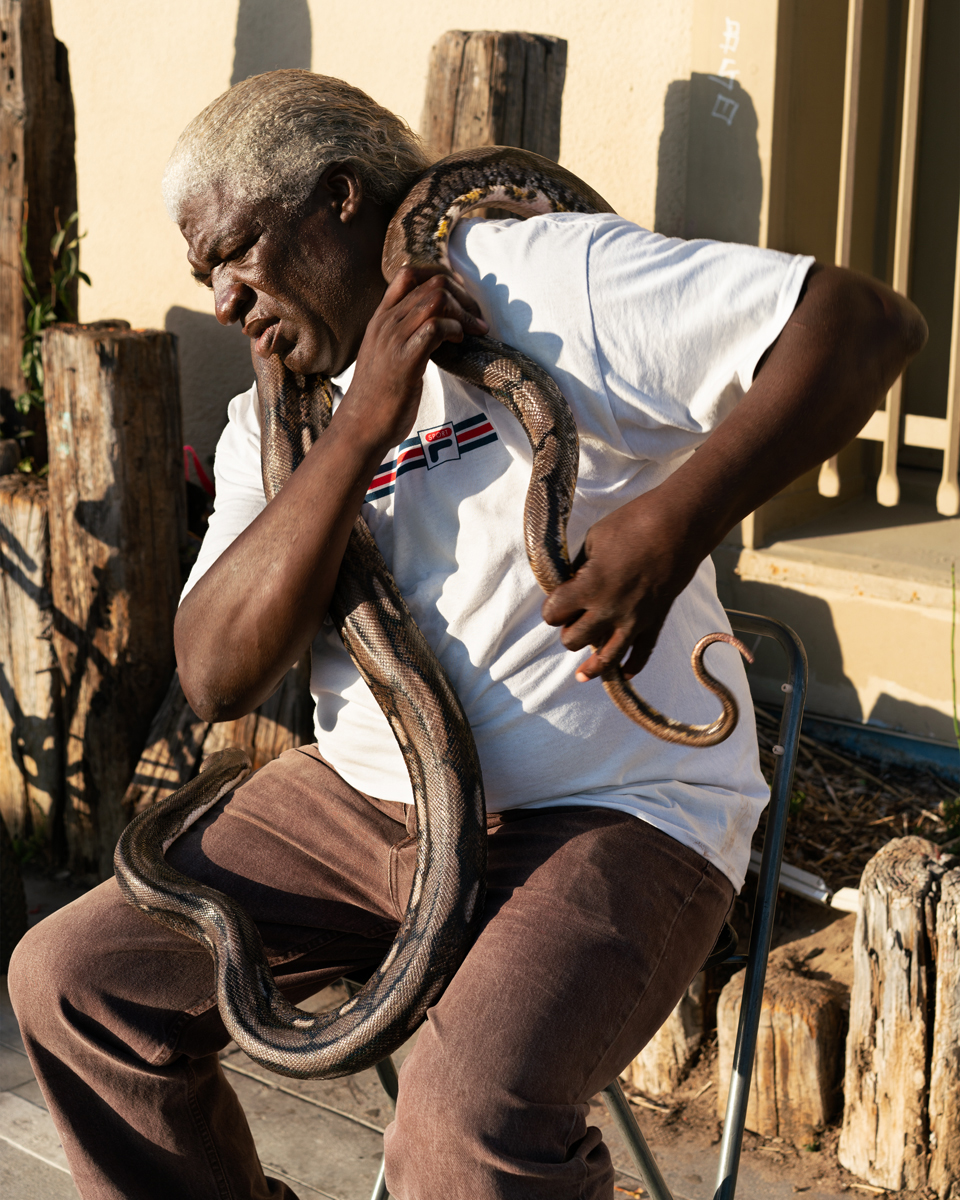 a man with a snake resting around his neck