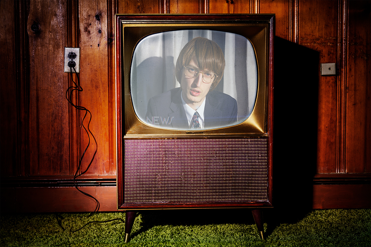 man wearing glasses on an old fashioned tv