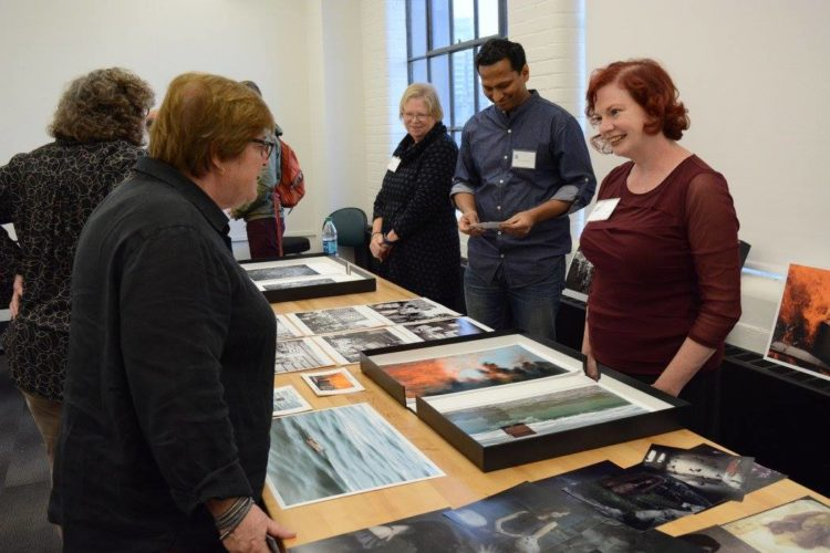 Photographers with portfolios on table