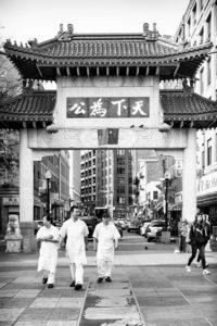 three men walking in chinatown boston - photograph