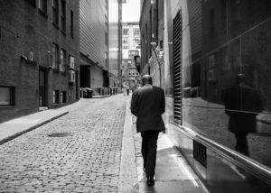 man walking down cobblestone street boston - photograph
