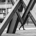 person walking behind sculpture - photograph