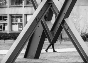 architectural detail with person walking visible behind sculpture - photograph