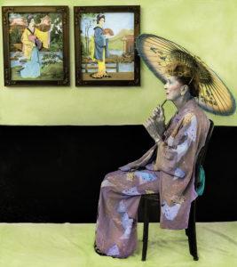 A woman dressed as a geisha with umbrella