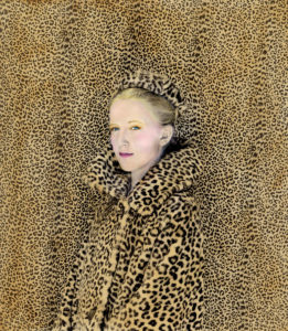 a woman in a leopard coat and hat