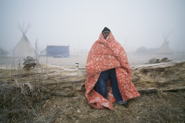 Man in blanket with teepee in background