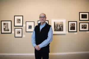 man in front of photographs