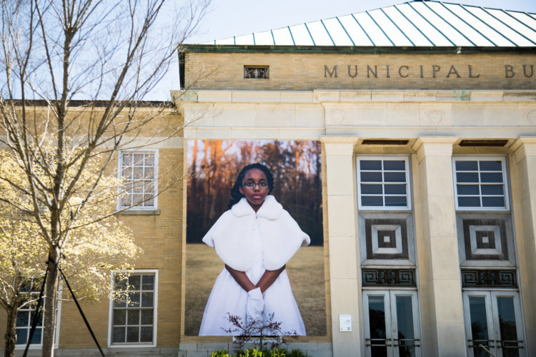 Large picture of girl in white dress hanging on building