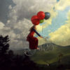 woman on bicycle with balloons